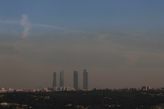 Pollution is seen above Madrid's skyline, including Cuatro Torres business area, or Four Towers, in this picture taken from the outskirts of the city